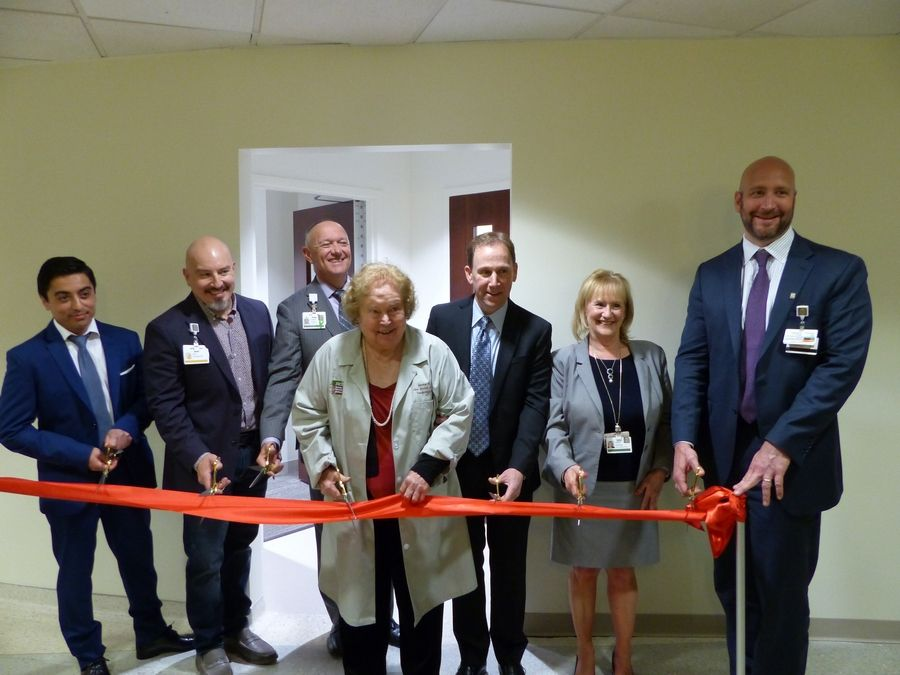 Martha Atherton, center, leads a group of doctors and administrators from Northwest Community Hospital in cutting the ribbon for the new hybrid cardiac catheterization lab.