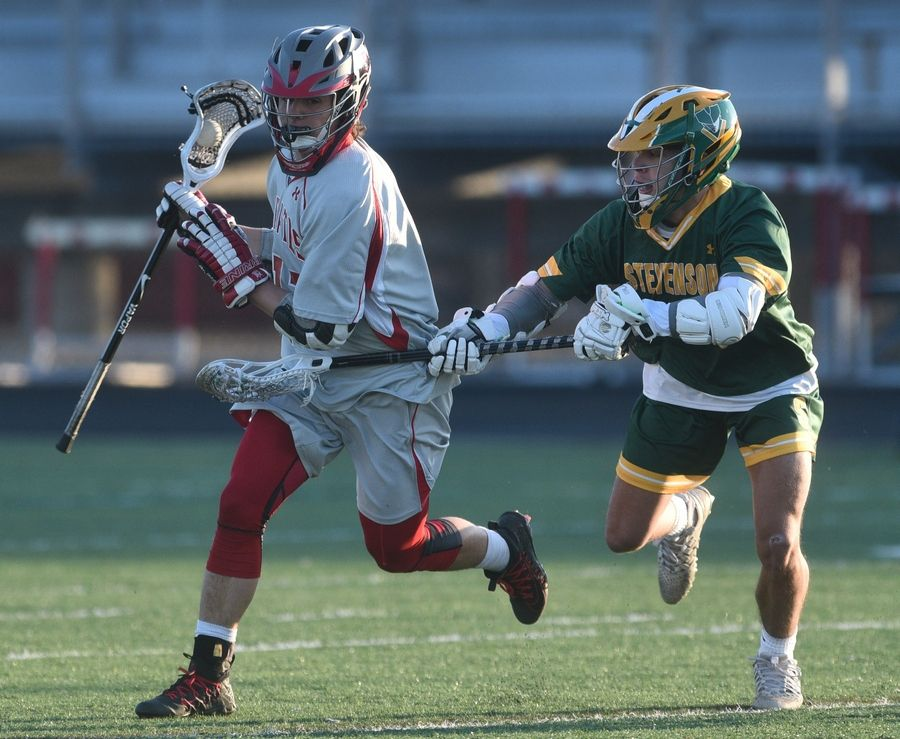 Palatine's Brady Foote, left, is pressured by Stevenson's Julio Adjunta during Monday's boy's lacrosse game in Palatine.
