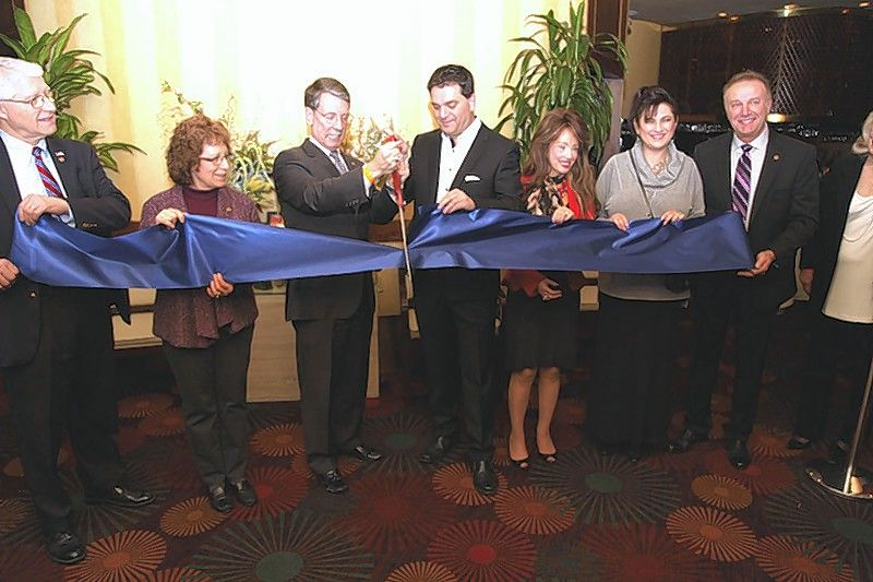 Surrounded by local dignitaries, Arlington Heights Mayor Tom Hayes, left, and George Theodossopoulos, owner and operating manager of Palm Court in Arlington Heights, cut the ribbon to signify a new beginning in the restaurant's 40-year history. Theodossopoulos took ownership of the restaurant in late 2018.