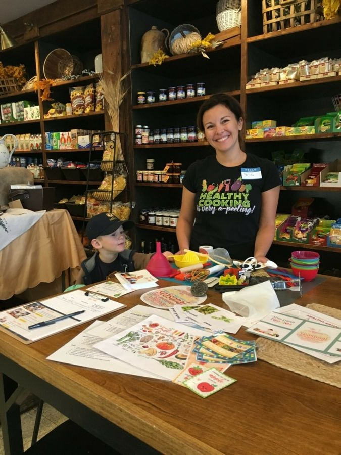 Perrine Quivron, owner of The Petit Foodies with son Timothee, shows samples of fun and educational materials used in class and kitchen tools that little hands are learning to use.