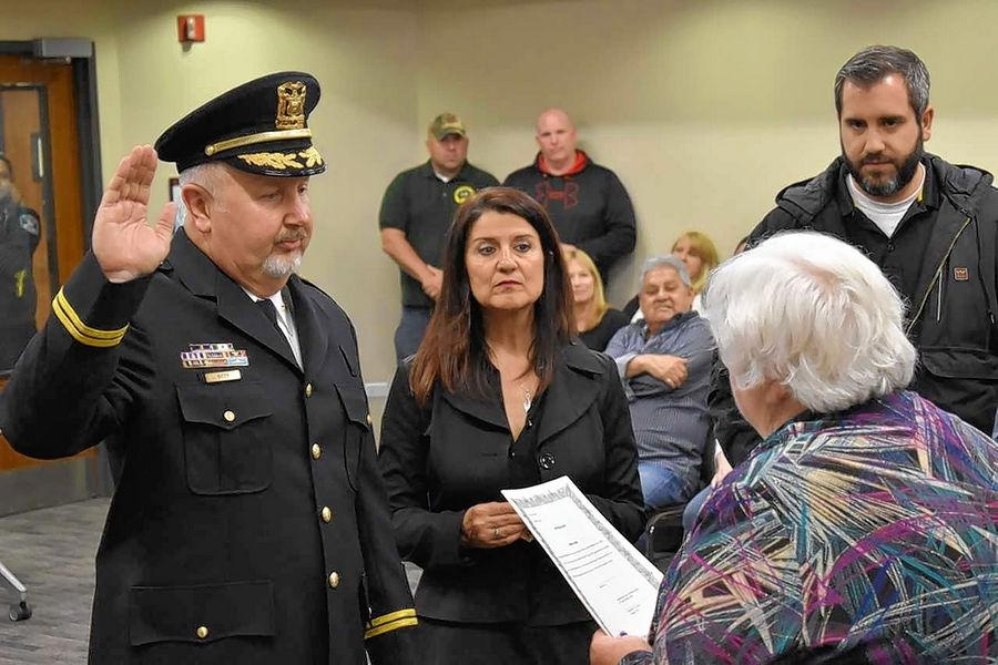 Mike Doty, left, formerly a police sergeant, was promoted last week to deputy chief in South Elgin. Next to him is his wife, Maria, and on far the right is his son Joshua.