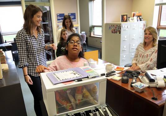 Student Shania Clement pushes a snack cart through the administrative offices at Wright Junior High School in Lincolnshire. Students with disabilities learn about counting money, providing goods and services, and social interactions by operating the cart twice a week.
