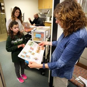 Student Mikayla Needlman, bottom left, hands payroll coordinator Chris Erickson a snack menu at Wright Junior High in Lincolnshire.