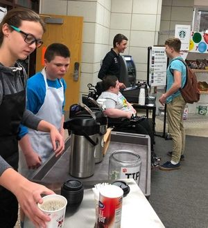 Libertyville High School student Anna Scholler and Chase Miller, both in foreground, prepare drinks while Brandon Fischer and Dan Keating serve a customer at the Wildcat Warehouse. The snack shop is operated by students in business classes and special-education programs.