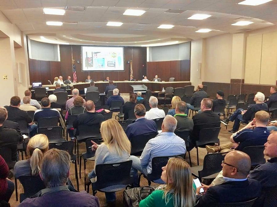 Spectators at Monday night's Palatine village council meeting watch a presentation on possible rules for video gambling.
