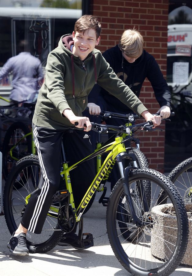 Naperville North High School junior Matas Skucas, 17, is all smiles Tuesday as he prepares to ride one of 40 new mountain bikes to his school, where a new cycling program will be integrated into the physical education curriculum.