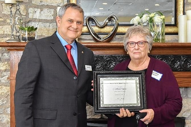 "Gretchen Vapnar, executive director of the Community Crisis Center, receives the Maureen Withers Award from chairman Alan Kirk at Ecker Center's ""Wishes for Wellness"" brunch April 14."