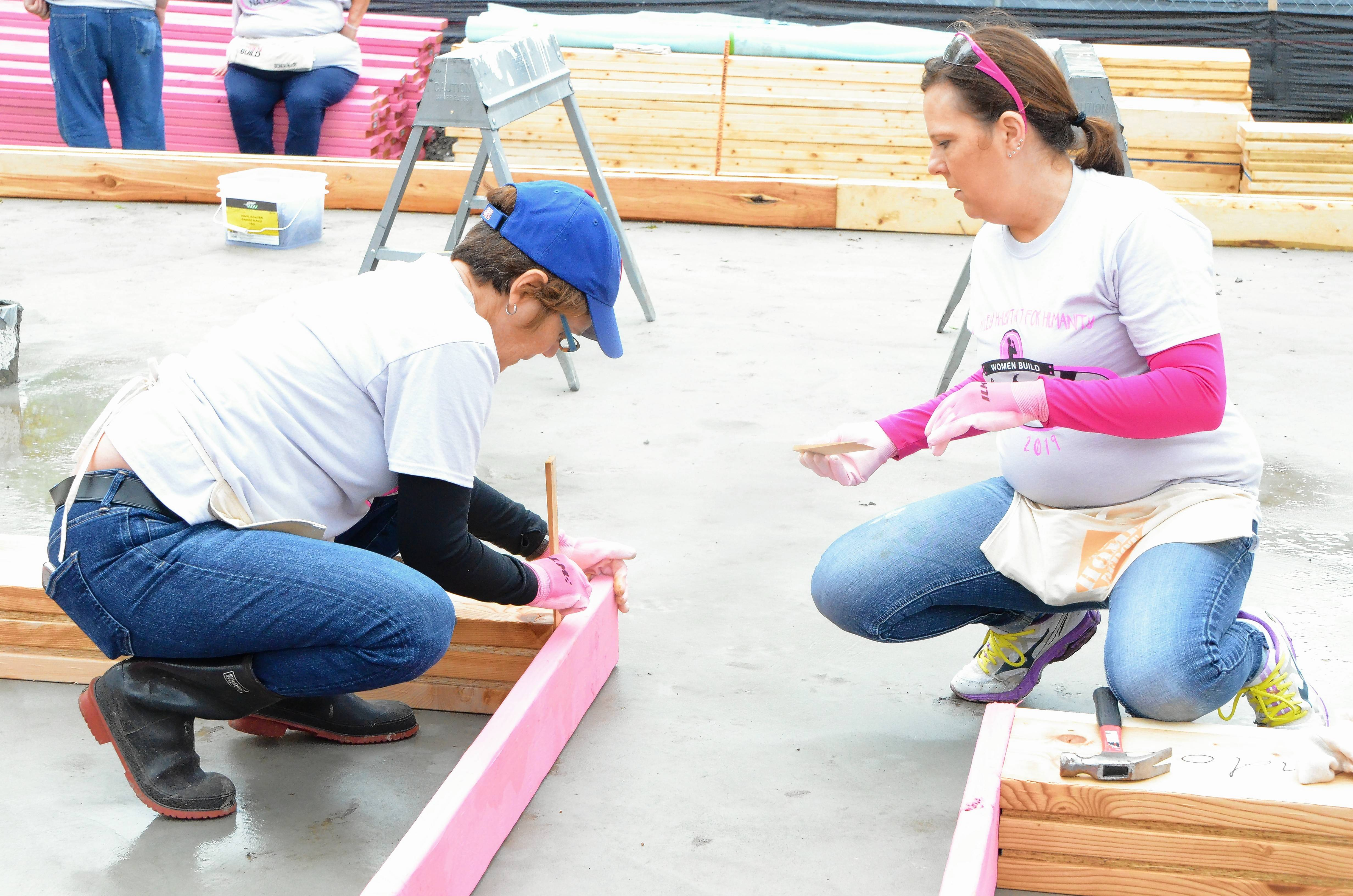 Batavia resident Rona Hunter-Foltos, left, and Katherine Bruck, Yorkville, team up during construction Thursday of Women Build 2019, a Fox Valley Habitat for Humanity home at 823 Gillette Ave. in Aurora. Twenty women launched construction of the frame ranch with detached garage.