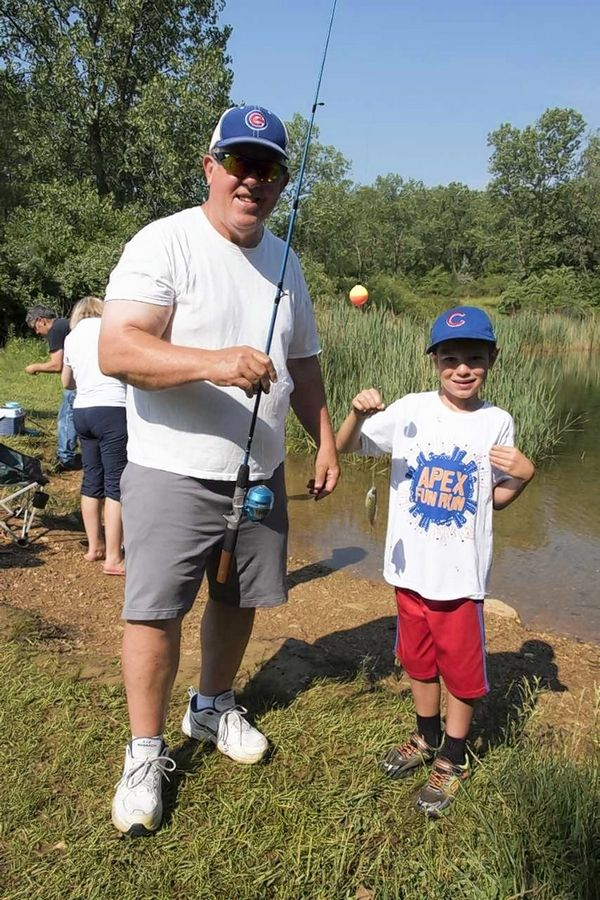 "Fish are measured for the 'biggest caught' contest and immediately released back into the lake at McHenry County Conservation District's ""Hooked on Fishing"" event."