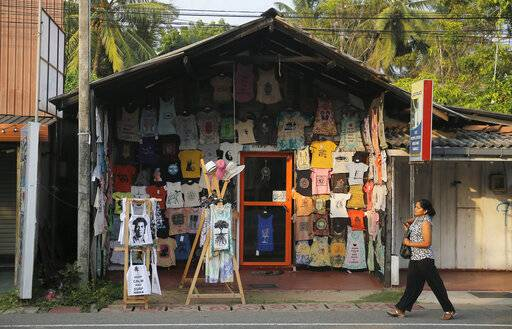 In this Friday, May 10, 2019, photo, a Sri Lankan walks past a souvenir shop in Hikkaduwa, Sri Lanka. Sri Lanka was the Lonely Planet guide's top travel destination for 2019, but since the Easter Sunday attacks on churches and luxury hotels, foreign tourists have fled. Hikkaduwa, in the south west, used to be top tourist attraction for the strong waves that were perfect for board-surfing and sparkling clear waters perfect for snorkeling. Today, of the 27 hotels, a very few are still open while most of others along with the eateries lining the six kilometer stretch of palm-fringed beach, are closed.