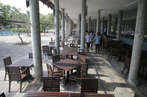 In this Friday, May 10, 2019, photo, hotel staff walk past an empty restaurant at a hotel in Hikkaduwa, Sri Lanka. Sri Lanka was the Lonely Planet guide's top travel destination for 2019, but since the Easter Sunday attacks on churches and luxury hotels, foreign tourists have fled. Hikkaduwa, in the south west, used to be top tourist attraction for the strong waves that were perfect for board-surfing and sparkling clear waters perfect for snorkeling. Today, of the 27 hotels, a very few are still open while most of others along with the eateries lining the six kilometer stretch of palm-fringed beach, are closed.