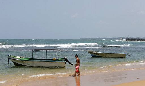 In this Friday, May 10, 2019, photo, a Ukrainian woman and a child walk past glass bottom boats, used for watching coral reefs, on a beach in Hikkaduwa, Sri Lanka. Sri Lanka was the Lonely Planet guide's top travel destination for 2019, but since the Easter Sunday attacks on churches and luxury hotels, foreign tourists have fled. Hikkaduwa, in the south west, used to be top tourist attraction for the strong waves that were perfect for board-surfing and sparkling clear waters perfect for snorkeling. Today, of the 27 hotels, a very few are still open while most of others along with the eateries lining the six kilometer stretch of palm-fringed beach, are closed.