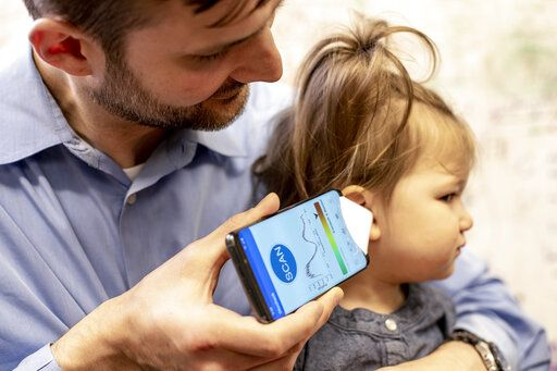 "In this undated photo provided by the University of Washington in May 2019, Dr. Randall Bly uses a uses a phone app and a paper funnel to focus the sound, to check his daughter for an ear infection, at the UW School of Medicine in Seattle. Bly and other researchers at the school have developed the system to ""hear� a warning sign of ear infections _ fluid build-up behind the eardrum. (Dennis Wise/University of Washington via AP)"