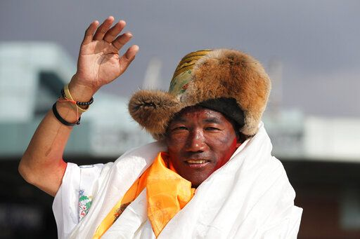 FILE - In this May 20, 2018, file photo, Nepalese veteran Sherpa guide, Kami Rita, 48, waves as he arrives in Kathmandu, Nepal. Rita has scaled Mount Everest for a 23rd time, breaking his own record for the most successful ascents of the world's highest peak.