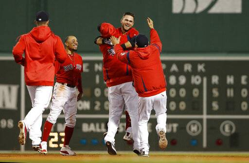 Boston Red Sox's Michael Chavis, second from right, is mobbed by teammates after his game-ending RBI single during the 10th inning of a baseball game against the Colorado Rockies on Wednesday, May 15, 2019, at Fenway Park in Boston. The Red Sox won 6-5.