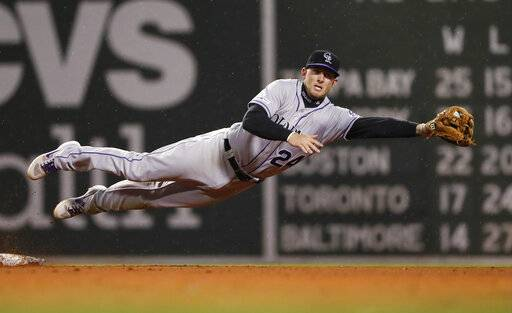 Colorado Rockies' Ryan McMahon leaps to grab a wide throw on a steal of second base by Boston Red Sox's Christian Vazquez during the fifth inning of a baseball game Wednesday, May 15, 2019, at Fenway Park in Boston.
