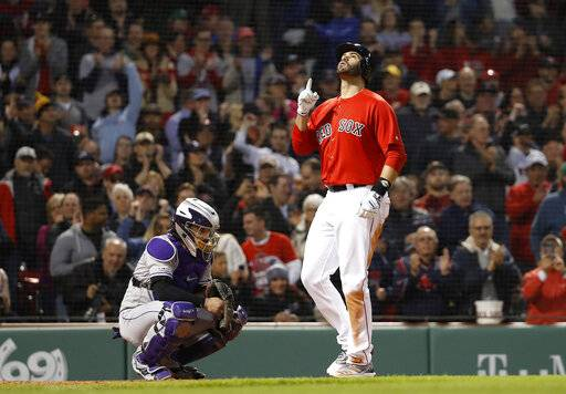 Boston Red Sox's J.D. Martinez points skyward as he crosses home plate in front of Colorado Rockies catcher Tony Wolters after his two-run home run during the third inning of a baseball game Wednesday, May 15, 2019, at Fenway Park in Boston.