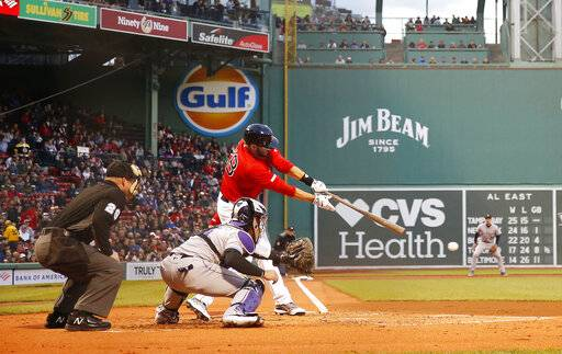 Boston Red Sox's J.D. Martinez connects for an RBI single against the Colorado Rockies during the first inning of a baseball game Wednesday, May 15, 2019, at Fenway Park in Boston.