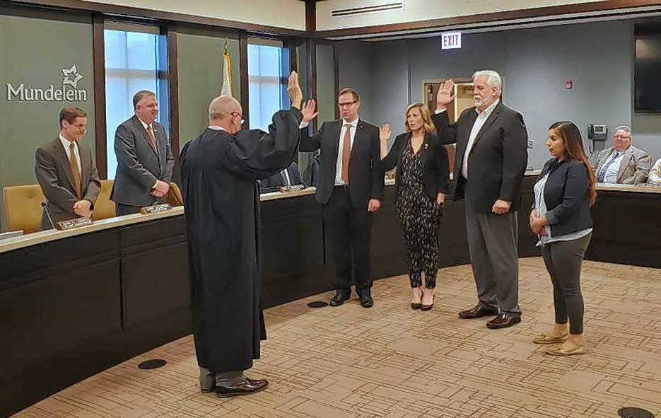 Lake County Judge Charles Smith, left, administers the oath of office on Monday to Mundelein Trustees Erich Schwenk, Kara Lambert and Kerston Russell. Village Clerk Sol Cabachuela stands at right.