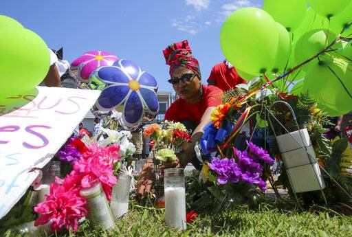Ahsaki Chachere arranges flowers Wednesday, May 15, 2019, at the memorial for Pamela Turner, who was killed Monday night during a confrontation with a Baytown Police officer at The Brixton Apartments complex in Baytown, Texas. (Godofredo A Vasquez/Houston Chronicle via AP)/Houston Chronicle via AP)