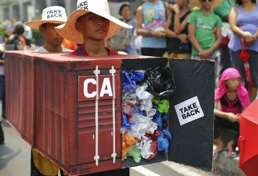 FILE - In this May 7, 2015, file photo, Filipino environmental activists wear a mock container vans filled with garbage to symbolize the 50 containers of waste that were shipped from Canada to the Philippines two years ago, as they hold a protest outside the Canadian embassy at the financial district of Makati, south of Manila, Philippines. The Philippine foreign secretary said Thursday, May 16, 2019, the ambassador and consuls in Canada are being recalled over Ottawa's failure to take back truckloads of garbage that Filipino officials say were illegally shipped to the Philippines years ago.