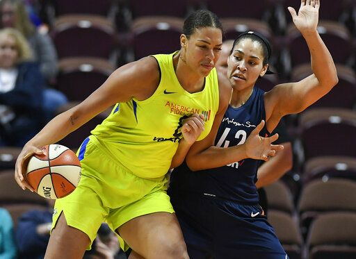 FILE - In this May 8, 2018, file photo, Dallas Wings' Liz Cambage, left, drives against Connecticut Sun's Brionna Jones during a preseason WNBA basketball game in Uncasville, Conn. A person familiar with the situation tells The Associated Press that the Dallas Wings have traded Liz Cambage to Las Vegas for Moriah Jefferson, Isabelle Harrison and the Aces' first two picks in 2020.  The person spoke on condition of anonymity Thursday, May 16, 2019, because the deal hasn't been announced.