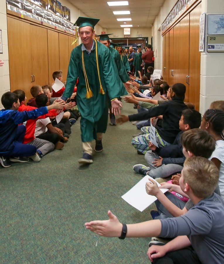 Fremd High School seniors in their caps and gowns greet young students during a visit to Hunting Ridge Elementary School in Palatine on Friday.