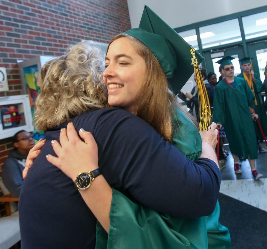 Sydney Lenz, a graduating senior at Fremd High School, gives former third-grade teacher Kristie Charles a hug during a visit to Hunting Ridge Elementary School in Palatine on Friday. Charles retired from the school in 2018 and came back to see the seniors walk through the school to inspire young children.