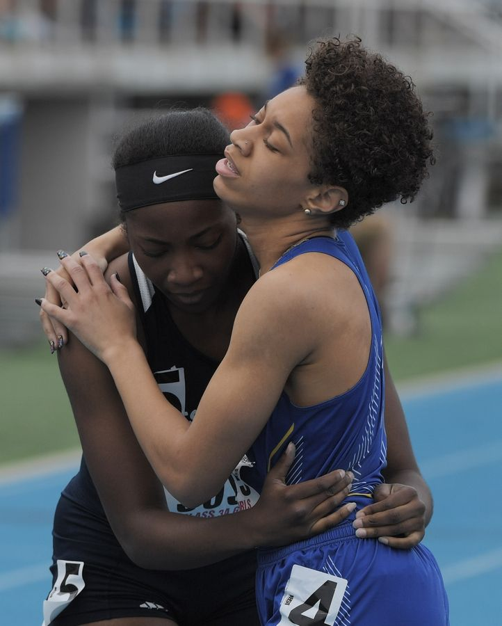 Warren's Janii Jenkins, right, hugs West Aurora's Dajour Miles at the conclusion of the 400-meter dash during the Class 3A girls state track and field preliminaries in Charleston Friday.