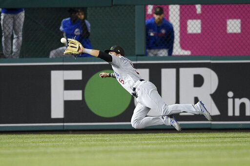 Chicago Cubs center fielder Albert Almora Jr. (5) dives for and catches a line drive by Washington Nationals' Juan Soto for an out during the ninth inning of a baseball game, Friday, May 17, 2019, in Washington.