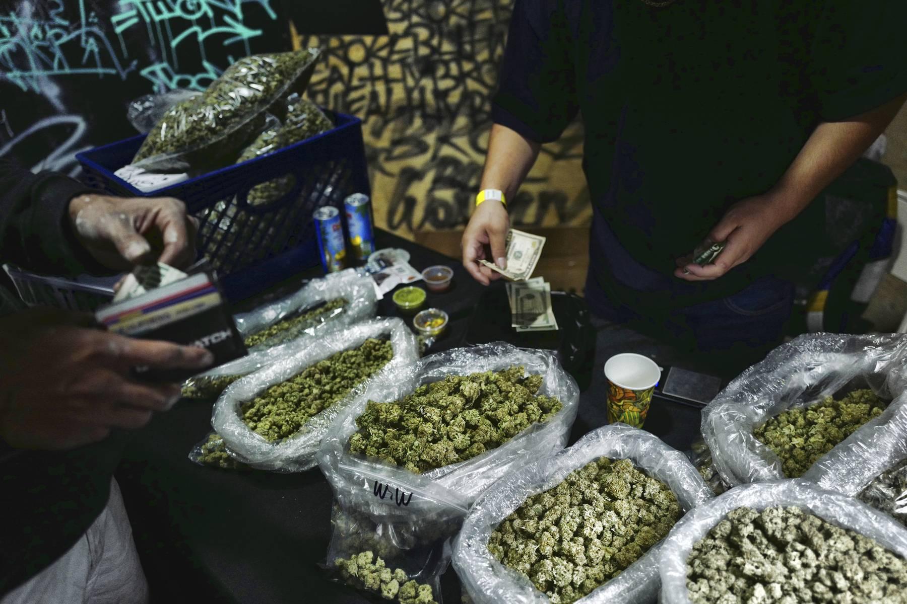 A vendor makes change for a marijuana customer at Rev-Up, a cannabis marketplace in Los Angeles.