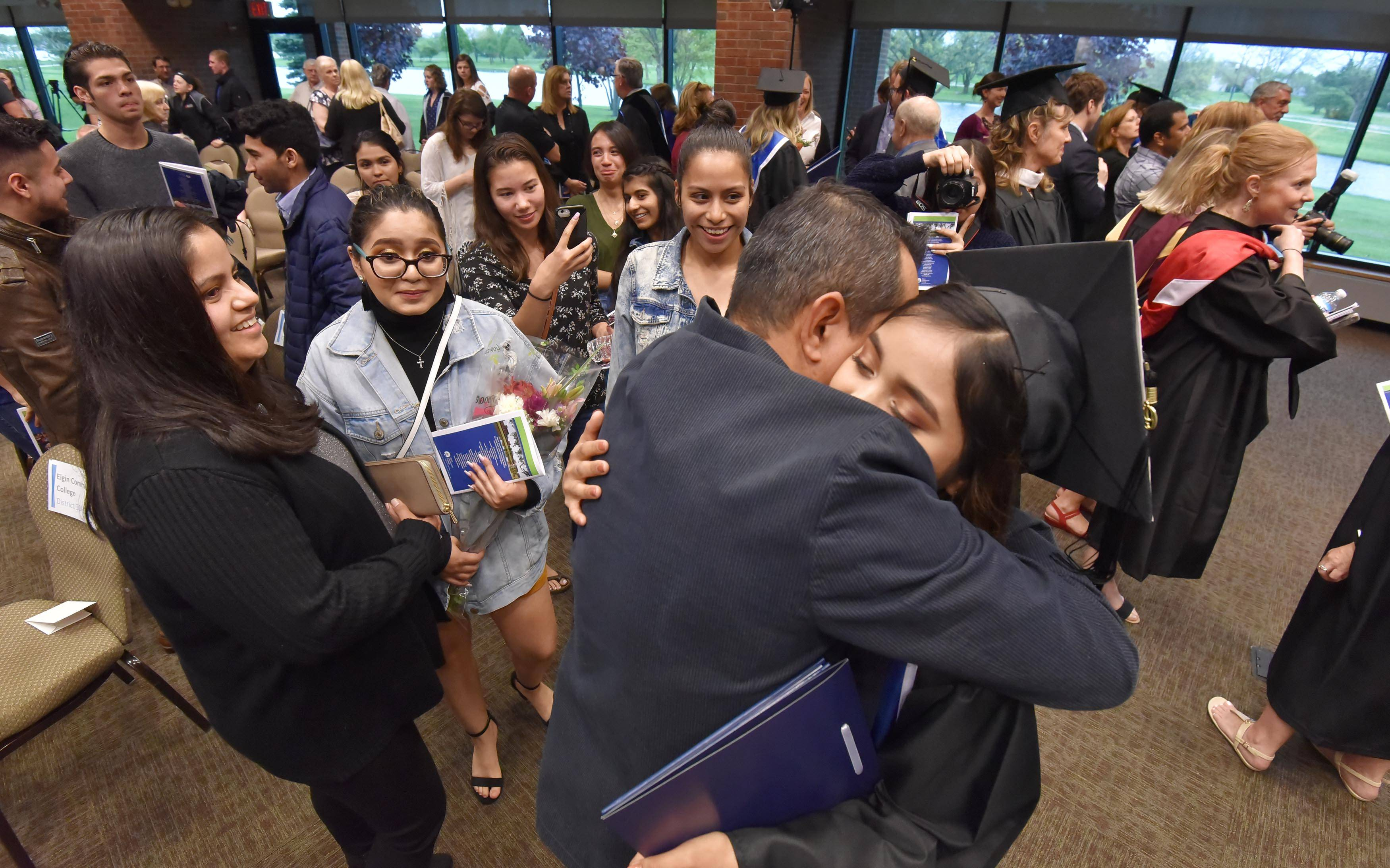 Anna Yessica Tello is hugged by her father, Guillermo, after she got her Associate of Arts degree from Elgin Community College on Friday. She was one of 10 Community Unit District 300 high school students to receive their associate degrees from ECC before getting their high school diplomas.