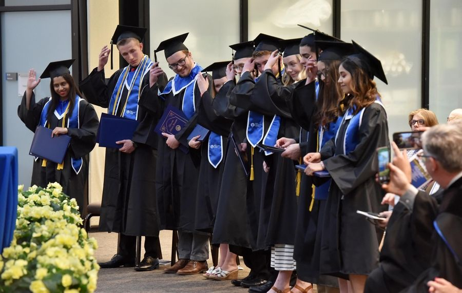 Ten Community Unit District 300 high school students switch their tassels as they receive their associate degrees from Elgin Community College Friday as the first graduating class of students to receive their degree before getting their high school diplomas.
