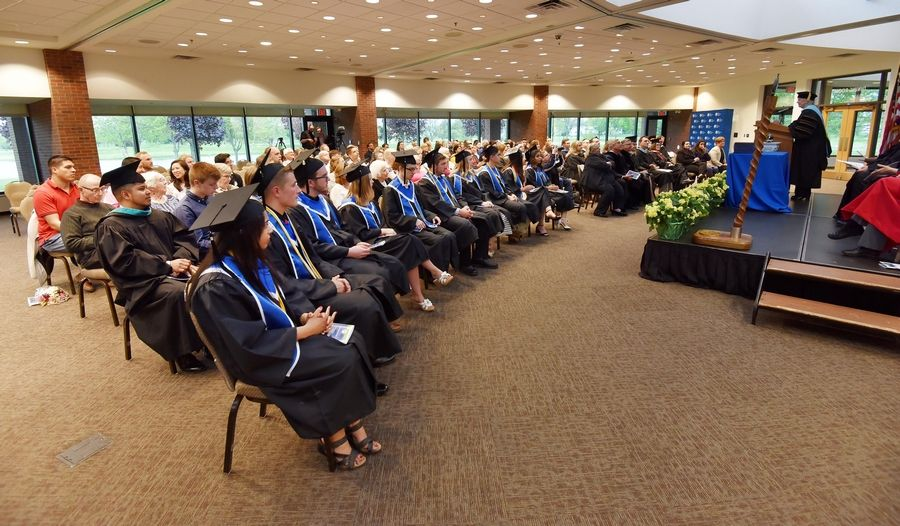 Ten Community Unit District 300 high school students sit during a ceremony to receive their associate degrees from Elgin Community College Friday. The are the first class to get a college degree before getting their high school diploma.