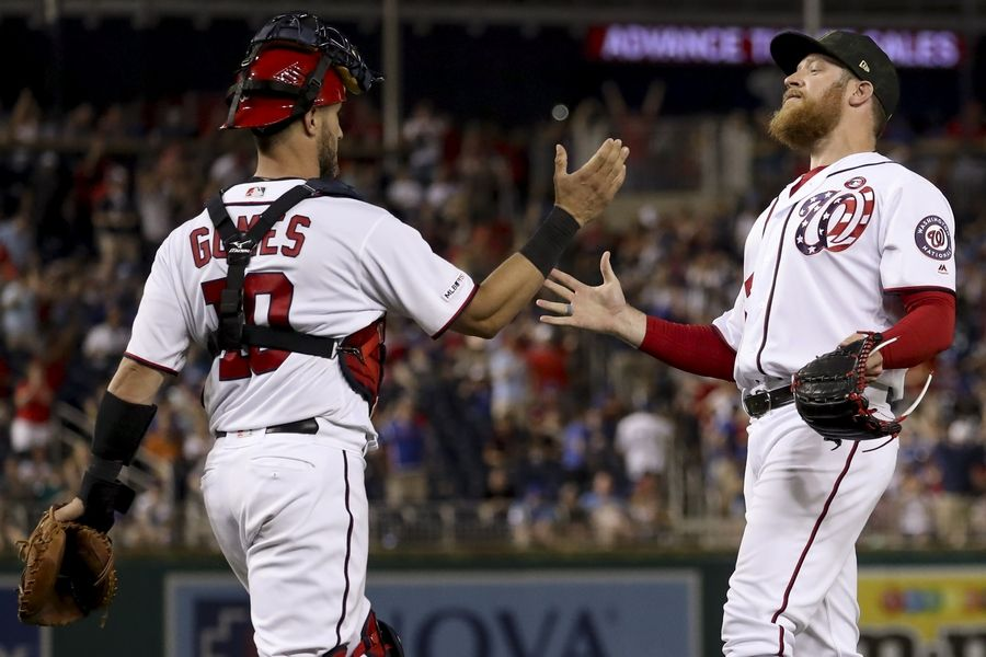 Washington Nationals catcher Yan Gomes (10) and Washington Nationals relief pitcher Sean Doolittle, right, celebrate after the Nationals defeated the Cubs 5-2 in Washington on Saturday.