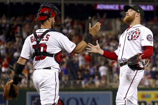 Washington Nationals catcher Yan Gomes (10) and Washington Nationals relief pitcher Sean Doolittle, right, celebrate after the Nationals defeated the Chicago Cubs 5-2 in a baseball game Saturday, May 18, 2019, in Washington.