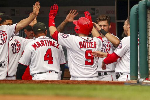 Washington Nationals' Brian Dozier (9) high-fives teammates after hitting a solo home run during the second inning of the team's baseball game against the Chicago Cubs, Saturday, May 18, 2019, in Washington.