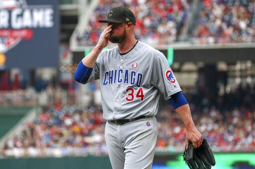 Chicago Cubs starting pitcher Jon Lester wipes his face as he walks off the field at the end of the second inning of the team's baseball game against the Washington Nationals, Saturday, May 18, 2019, in Washington.