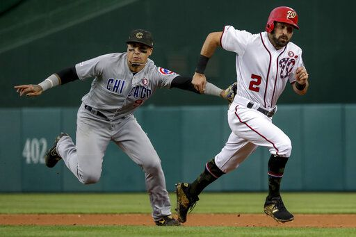 Washington Nationals' Adam Eaton (2) is tagged out by Chicago Cubs shortstop Javier Baez after trying to steal second during the third inning of a baseball game Saturday, May 18, 2019, in Washington.