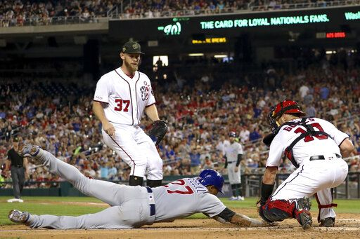 Washington Nationals starting pitcher Stephen Strasburg (37) watches as catcher Yan Gomes (10) tags out Chicago Cubs' Addison Russell (27) who tried to score on a passed ball during the fifth inning of a baseball game Saturday, May 18, 2019, in Washington.