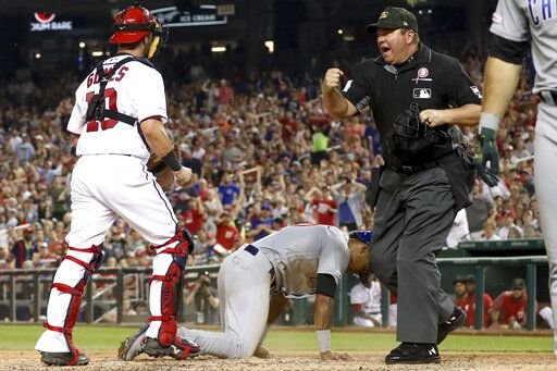 Umpire Sam Holbrook calls out Chicago Cubs' Addison Russell (27) after Washington Nationals catcher Yan Gomes (10) tagged him out after a passed ball to end the top of the fifth inning of a baseball game Saturday, May 18, 2019, in Washington.