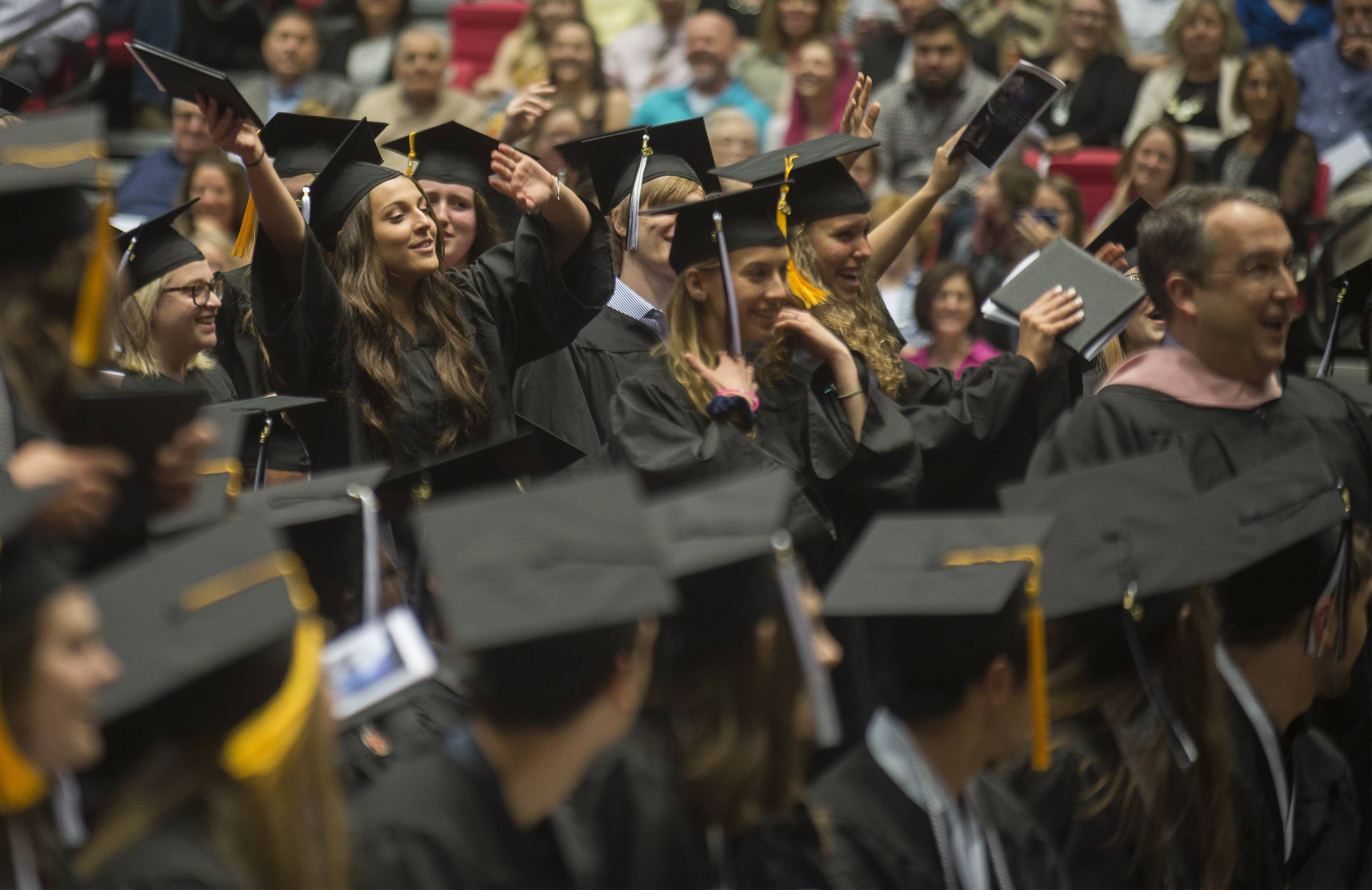 "Graduates sing along as madrigals perform the song ""Africa"" during graduation Sunday, May 19 in the Convocation Center at Northern Illinois University."