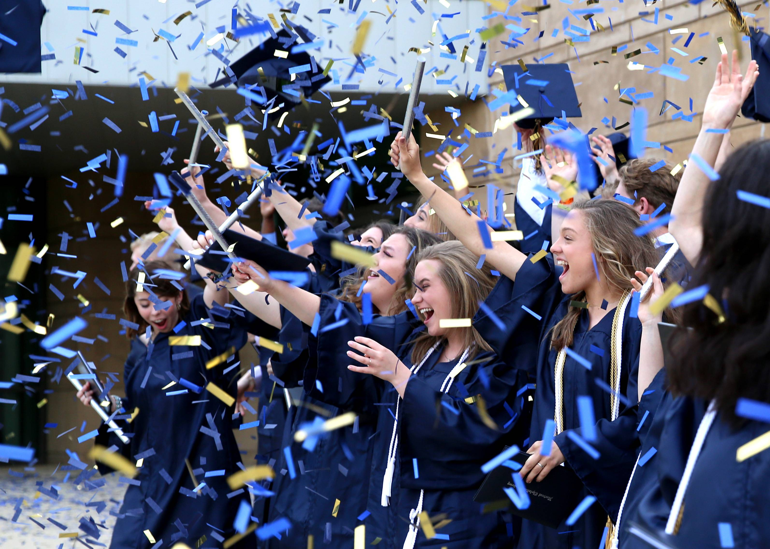 Graduates toss their caps amidst a confetti storm after Harvest Christian Academy graduation on Sunday, May 19, 2019 at the school campus in Elgin.