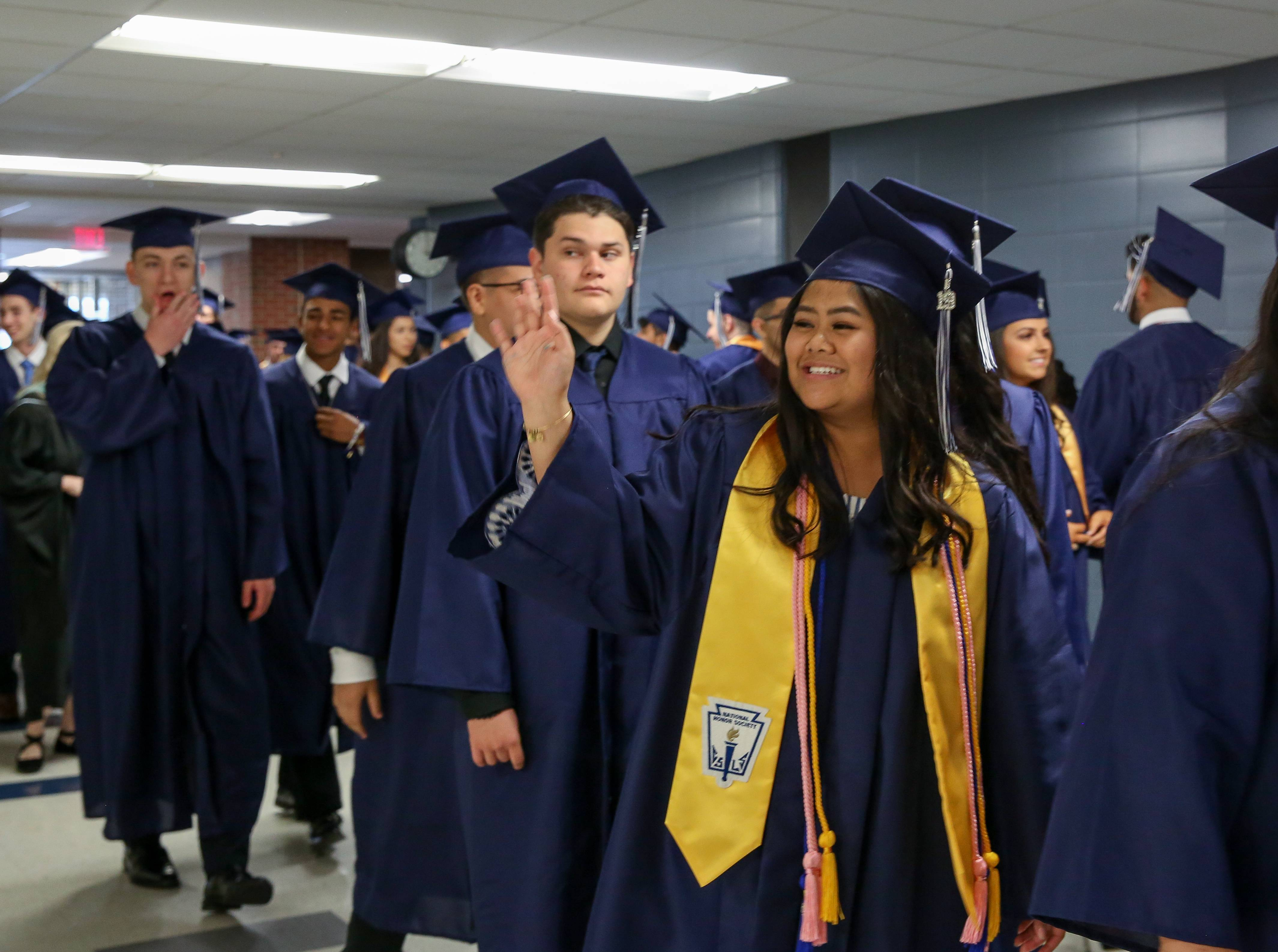 Rosemarie Mercado gives a wave as graduates file in for the Addison Trail High School graduation on Sunday at the school.