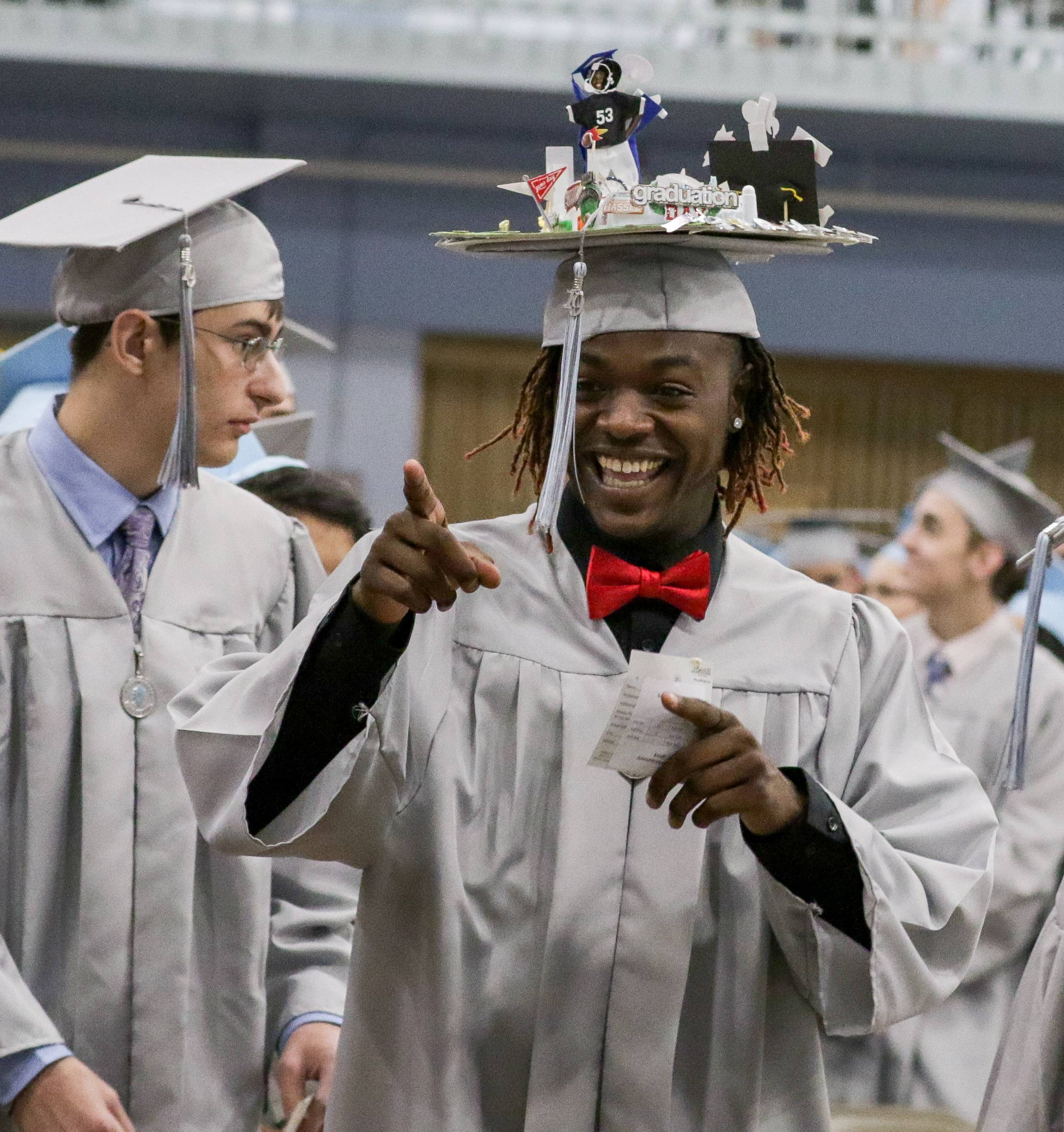 Dulane Hampton Caffrey, Jr., sees his family as he files in for the Willowbrook High School graduation on Sunday at the school in Villa Park. Caffrey was a member of the football team.