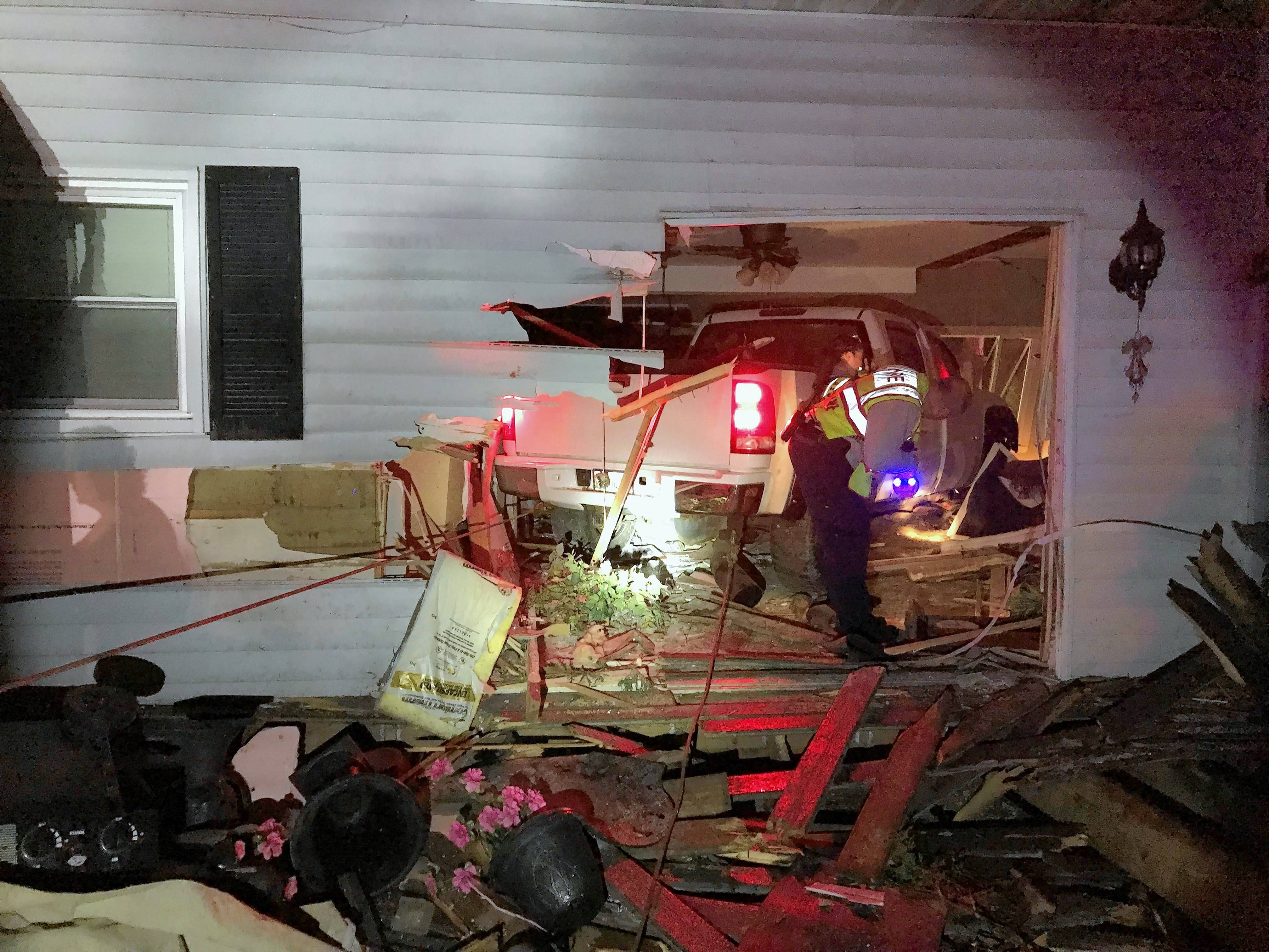 A pickup truck slammed into this home near Spring Grove early Sunday, leaving a sleeping 71-year-old resident pinned under the vehicle.