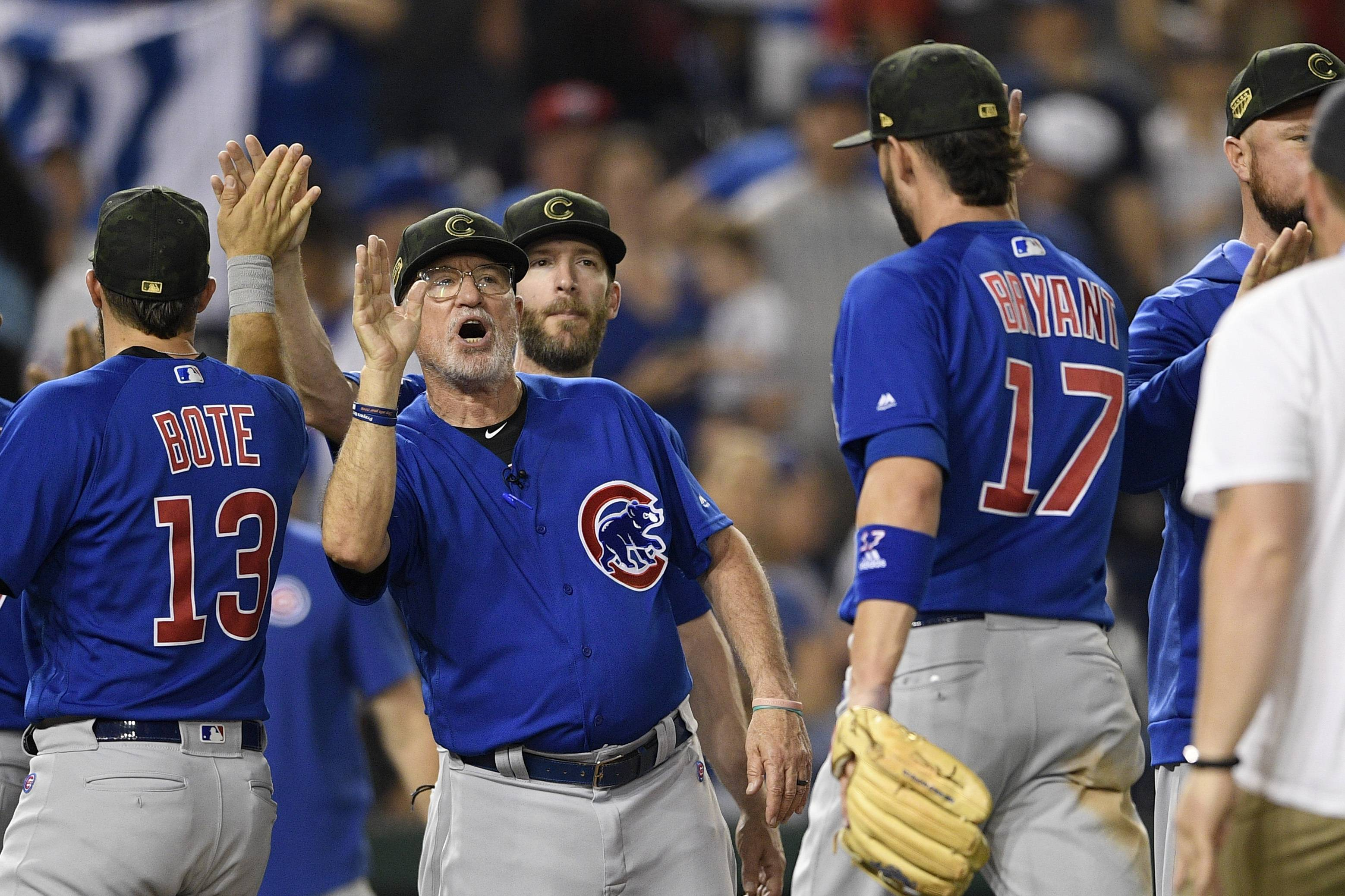 Chicago Cubs manager Joe Maddon, left, celebrates with Kris Bryant (17) after a baseball game against the Washington Nationals, Sunday, May 19, 2019, in Washington. The Cubs won 6-5. (AP Photo/Nick Wass)