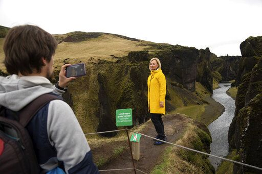 In this photo taken Wednesday, May 1, 2019, Russian tourist Nadia Kazachenok poses for a photograph taken by Mikhail Samarin at the Fjadrárgljúfur. The canyon is closed, with roadblocks and rope fences, but tourists were quick to pass when the ranger went off duty on a Wednesday afternoon.