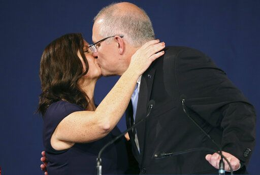 Australian Prime Minister Scott Morrison, right, kisses his wife, Jenny, after his opponent conceded defeat in the federal election in Sydney, Australia, Sunday, May 19, 2019. Australia's ruling conservative coalition, lead by Morrison, won a surprise victory in the country's general election, defying opinion polls that had tipped the center-left opposition party to oust it from power and promising an end to the revolving door of national leaders.