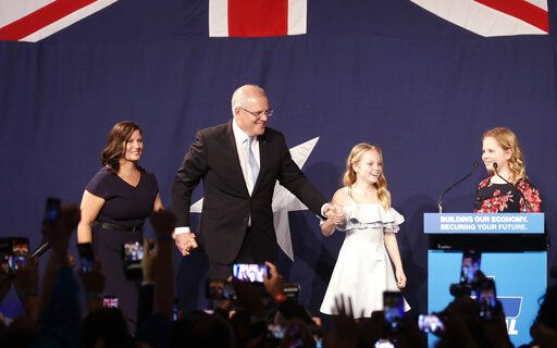 Australian Prime Minister Scott Morrison, second left, arrives on stage to speak to party supporters flanked by his wife, Jenny, left, and daughters Lily, and Abbey, right, after his opponent conceded in the federal election in Sydney, Australia, Sunday, May 19, 2019. Australia's ruling conservative coalition, lead by Morrison, won a surprise victory in the country's general election, defying opinion polls that had tipped the center-left opposition party to oust it from power and promising an end to the revolving door of national leaders.